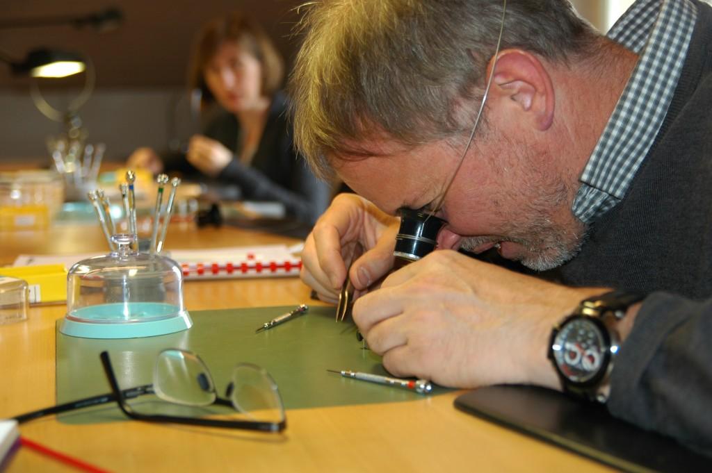 Charles, conseil en brevet, concentré pendant le remontage d'une montre